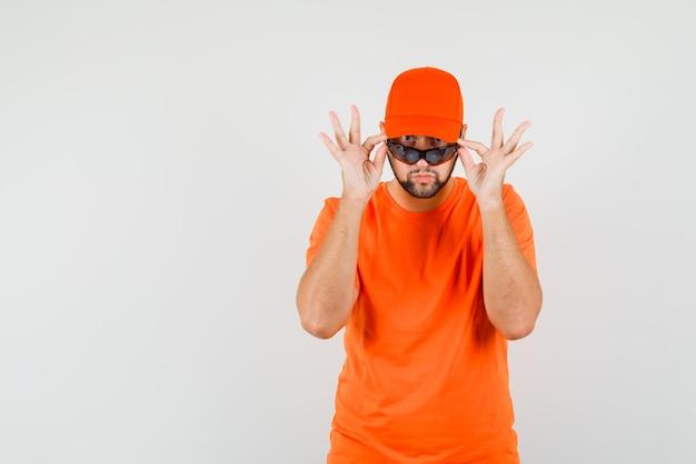 Fattorino guardando sopra gli occhiali in maglietta arancione, berretto e guardando dubbioso. vista frontale.