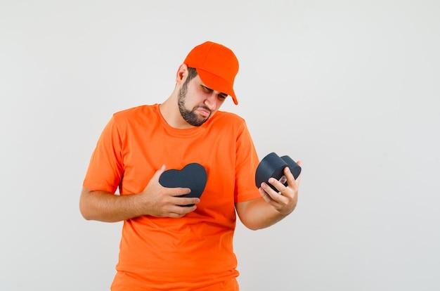 Uomo di consegna che esamina scatola regalo in maglietta arancione, berretto e sembra deluso, vista frontale.
