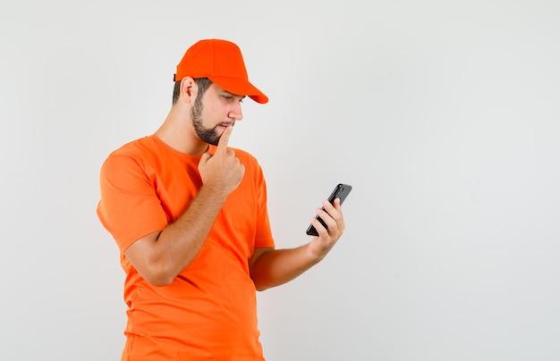 Fattorino che guarda il cellulare in maglietta arancione, berretto e sembra pensieroso. vista frontale.