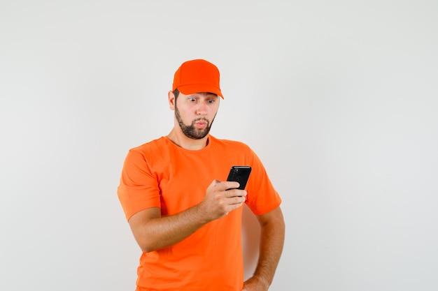 Uomo di consegna guardando il cellulare in t-shirt, berretto e guardando domandato. vista frontale.
