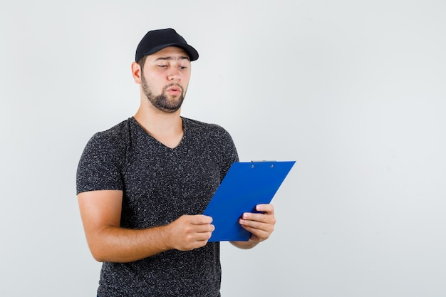 Delivery man looking over notes on clipboard in t-shirt and cap and looking careful