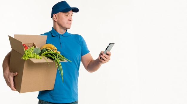 Delivery man looking at smartphone while carrying grocery box