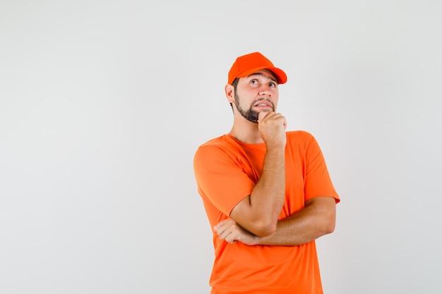 オレンジ色のtシャツ、キャップ、物思いにふける彼のあごを保持しながら見上げる配達人。正面図。