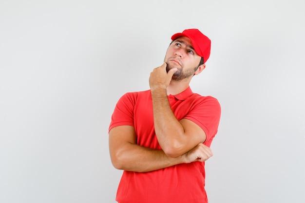 赤いtシャツのあごに触れながら見上げる配達人