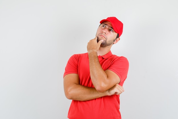 Uomo di consegna che osserva in su mentre tocca il mento in maglietta rossa