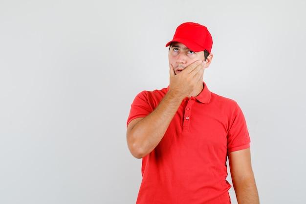 Uomo di consegna che osserva in su con la mano sulla faccia in maglietta rossa