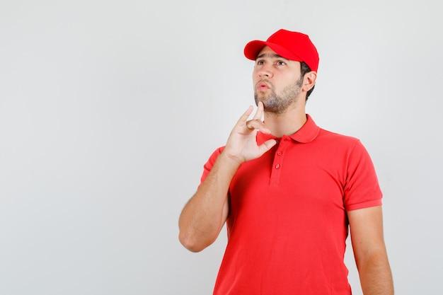 Uomo di consegna che guarda verso l'alto con il dito sul mento in maglietta rossa