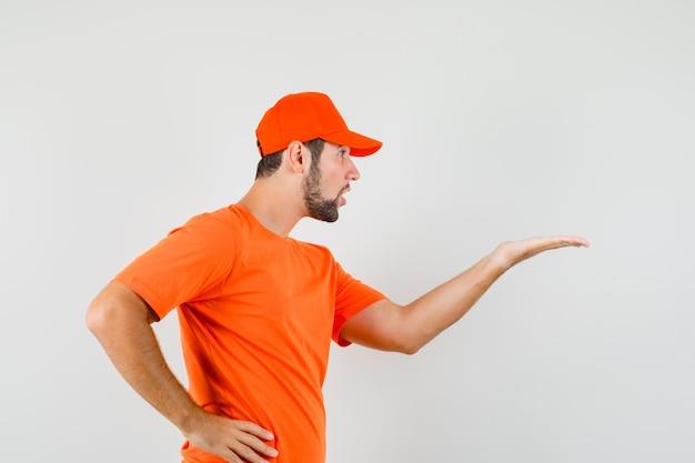 Доставщик делает вопросительный жест в оранжевой футболке, кепке и выглядит смущенным.