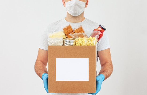 Delivery man in a mask and medical gloves holds a box of provisions