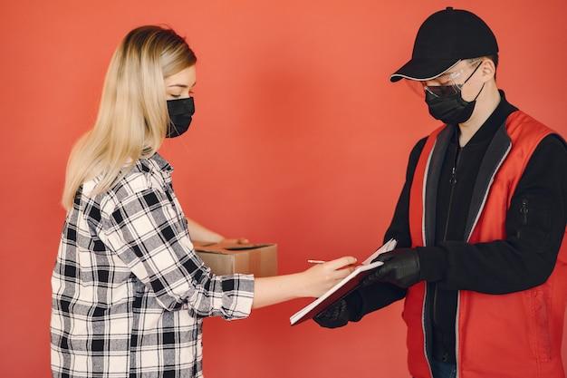 Uomo di consegna in una maschera medica con donna