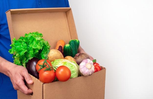 Разносчик свежих овощей в синей форме на белом