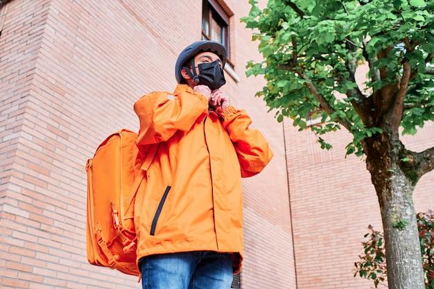 Доставщик на велосипеде и защитный рюкзак с маской для лица надевает шлем