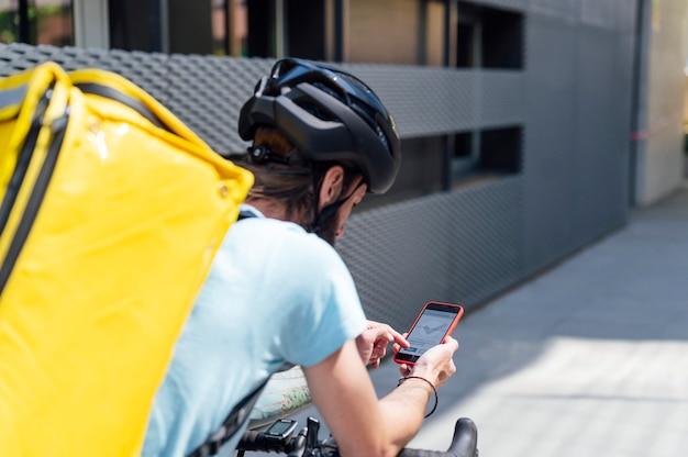 Доставщик на велосипеде с мобильным телефоном