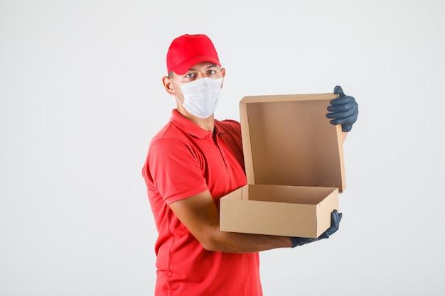 Uomo di consegna apertura scatola di cartone in uniforme rossa, mascherina medica, guanti