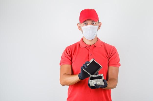 Uomo di consegna che apre la scatola attuale in uniforme rossa, mascherina medica, guanti.
