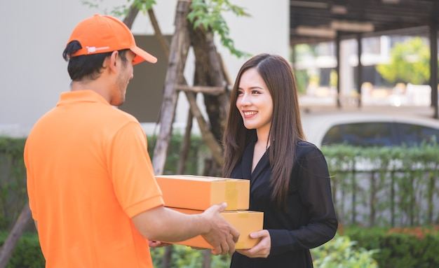 Delivery man in orange bringing woman the package Premium Photo
