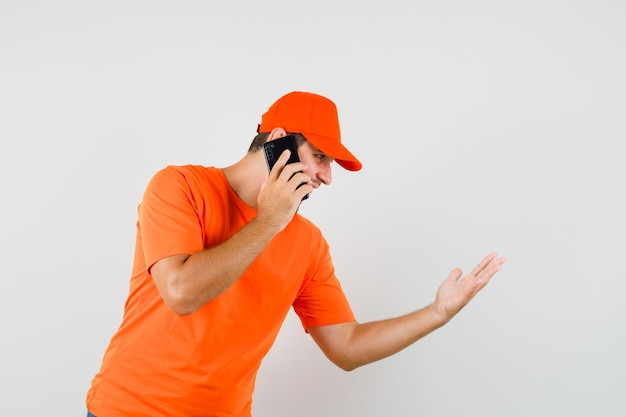 Fattorino in maglietta arancione, berretto che discute qualcosa sul telefono cellulare, vista frontale.