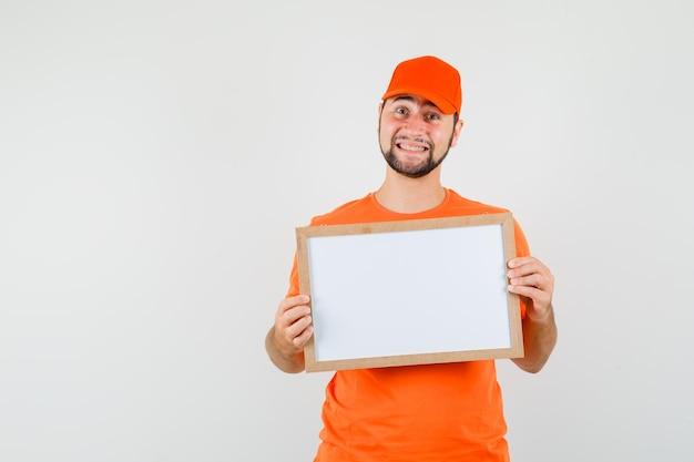 Fattorino in maglietta arancione, berretto che tiene una cornice vuota e sembra allegro, vista frontale.