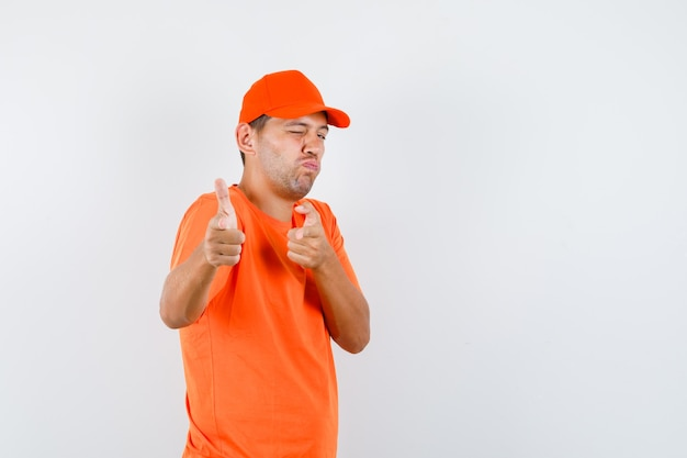 Delivery man in orange t-shirt and cap imitating gun gesture