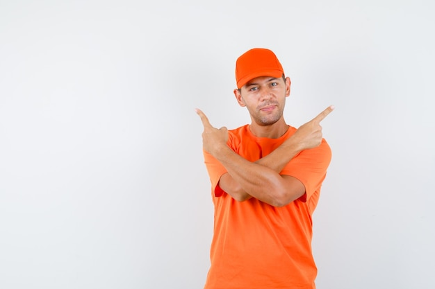Delivery man in orange t-shirt and cap pointing away and looking sure