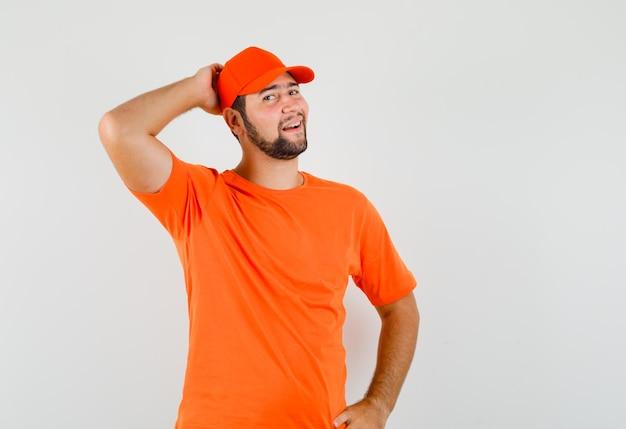 Fattorino in maglietta arancione, berretto in posa con la mano dietro la testa e dall'aspetto elegante, vista frontale.