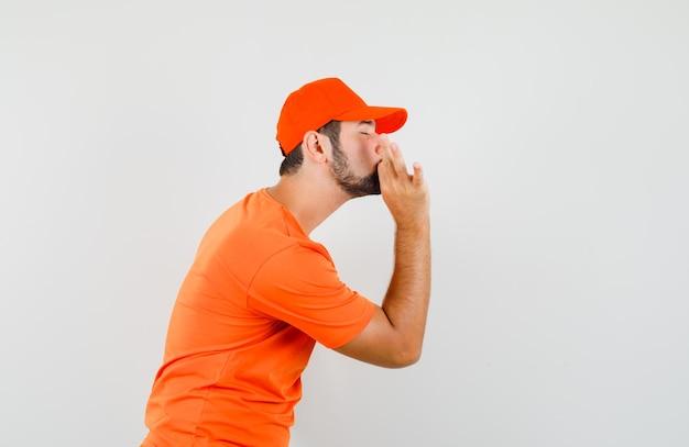 Fattorino in maglietta arancione, berretto che mostra un gesto delizioso e sembra felice.