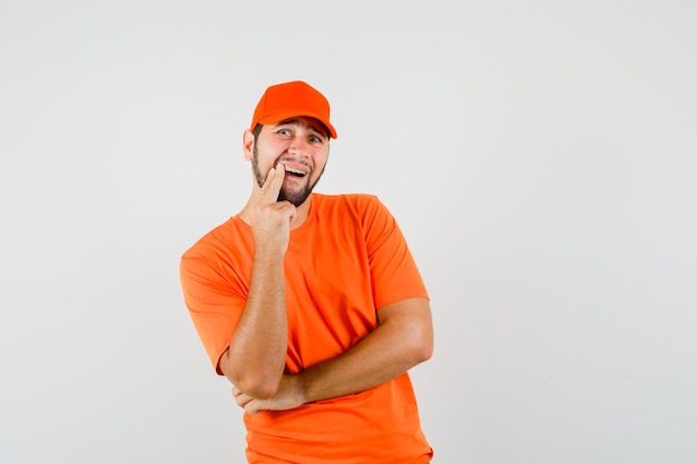 Delivery man in orange t-shirt, cap showing painful tooth and looking uncomfortable , front view.