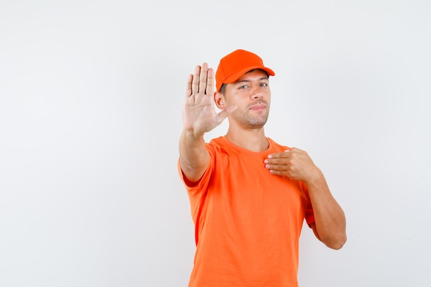 Delivery man in orange t-shirt and cap showing stop gesture by pointing at himself and looking confident