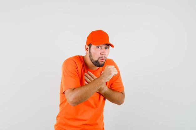 Uomo delle consegne in maglietta arancione, berretto che soffre di tosse e sembra malato, vista frontale.