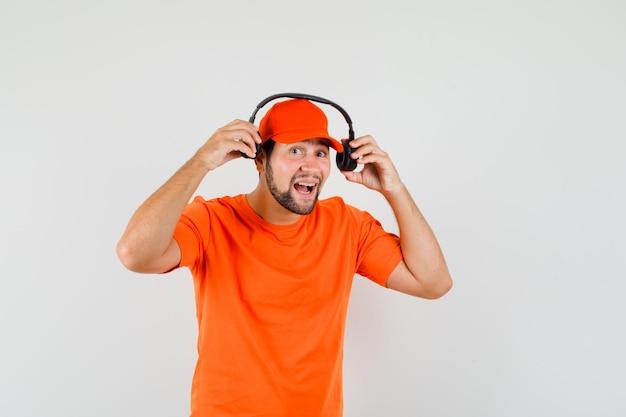Fattorino in maglietta arancione, berretto con le cuffie e guardando allegro, vista frontale.