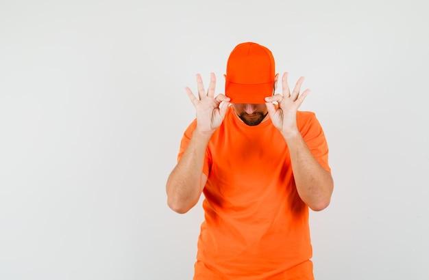 Uomo delle consegne in maglietta arancione che tira giù il berretto sugli occhi e sembra fresco, vista frontale.