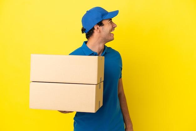 横の位置で笑っている孤立した黄色の壁の上の配達人