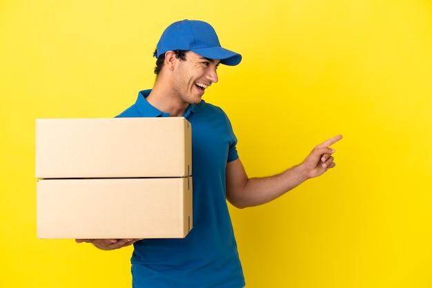 Доставщик над изолированной желтой стеной, указывая пальцем в сторону и представляя продукт