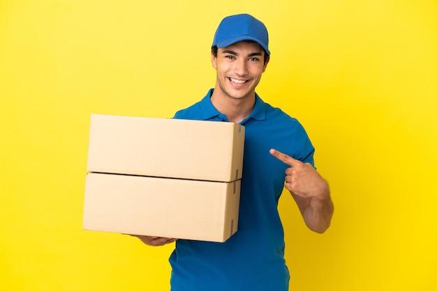 製品を提示する側を指している孤立した黄色の壁の上の配達人