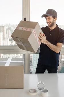 顧客に出荷するための小包を梱包する配達人