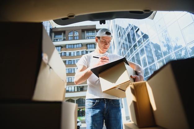 Доставщик, собирающий коробку из машины.