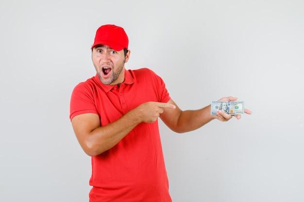 赤いtシャツでドル紙幣を指している配達人