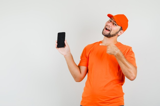 주황색 티셔츠, 모자를 쓰고 쾌활한 표정으로 휴대폰을 가리키고 있는 배달원. 전면보기.
