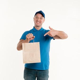 Доставка человек, указывая на бумажный пакет