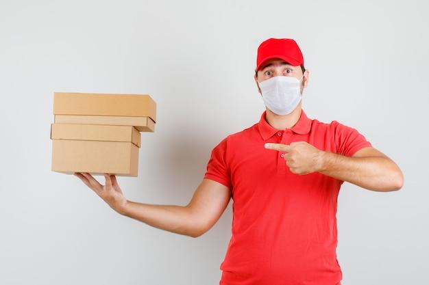 Uomo di consegna che indica a scatole di cartone in maglietta rossa