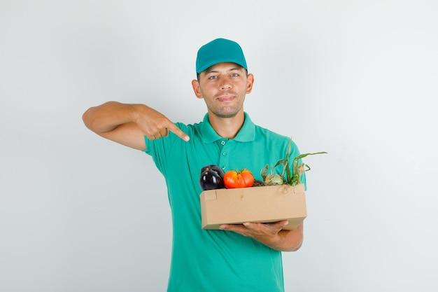Доставщик, указывая пальцем на овощную коробку в зеленой футболке с кепкой