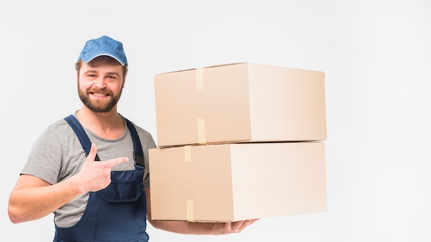 Delivery man pointing finger at boxes