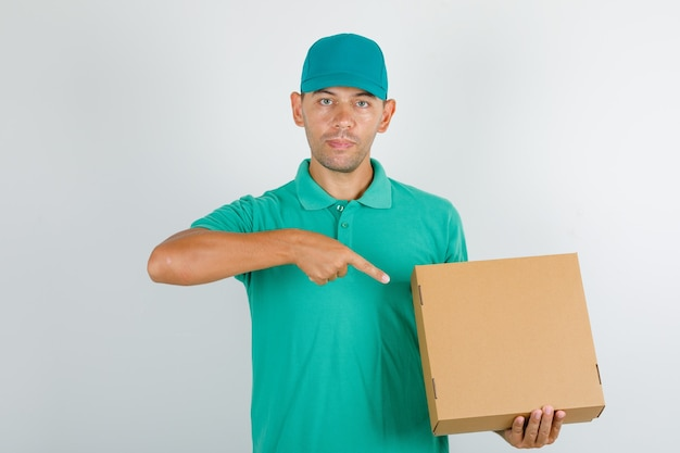 Delivery man pointing finger at cardboard box in green t-shirt with cap