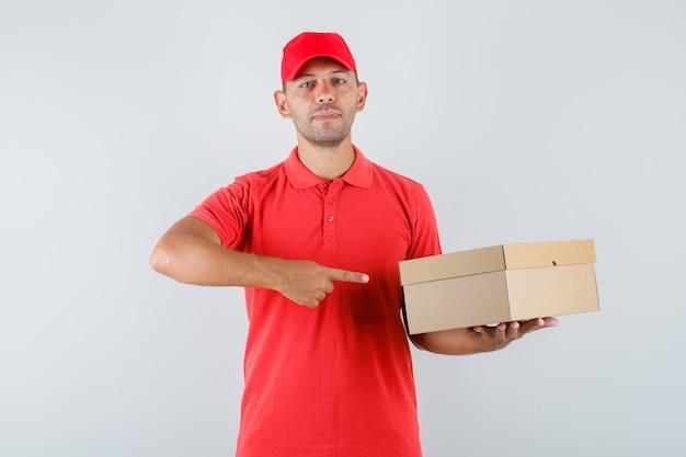 Uomo di consegna puntare il dito contro la scatola di cartone in berretto rosso e t-shirt e guardando fiducioso