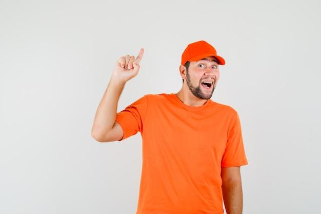배달원은 주황색 티셔츠, 모자를 쓰고 즐거운 표정을 짓고 앞모습을 가리키고 있습니다.