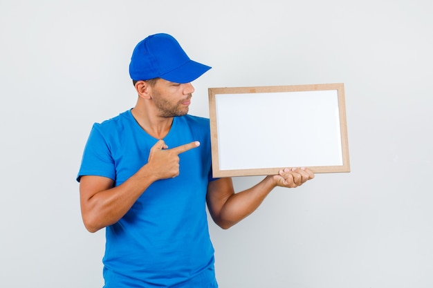 Delivery man pointing finger at white board in blue t-shirt