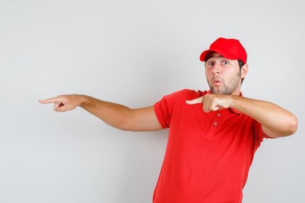 Uomo di consegna che punta le dita via in maglietta rossa