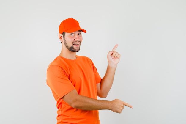 주황색 티셔츠, 모자를 쓰고 쾌활한 표정으로 손가락을 위아래로 가리키는 배달원. 전면보기.