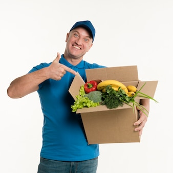 Delivery man pointing to grocery box
