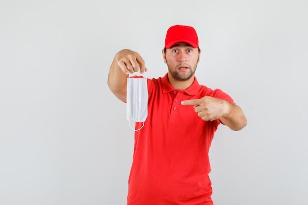 Uomo di consegna che indica alla mascherina medica in maglietta rossa Foto Gratuite